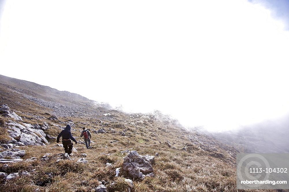Two people hiking through a mountain scenery, Oberstdorf, Bavaria, Germany