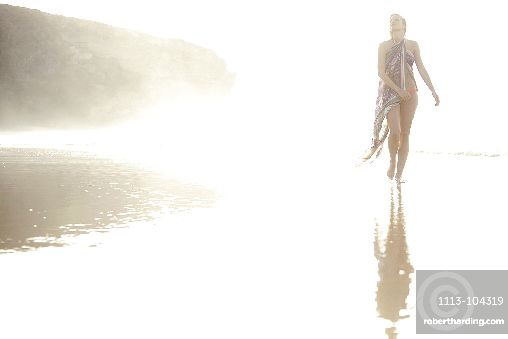 Young woman walking through shallow water at beach, Fuerteventura, Spain