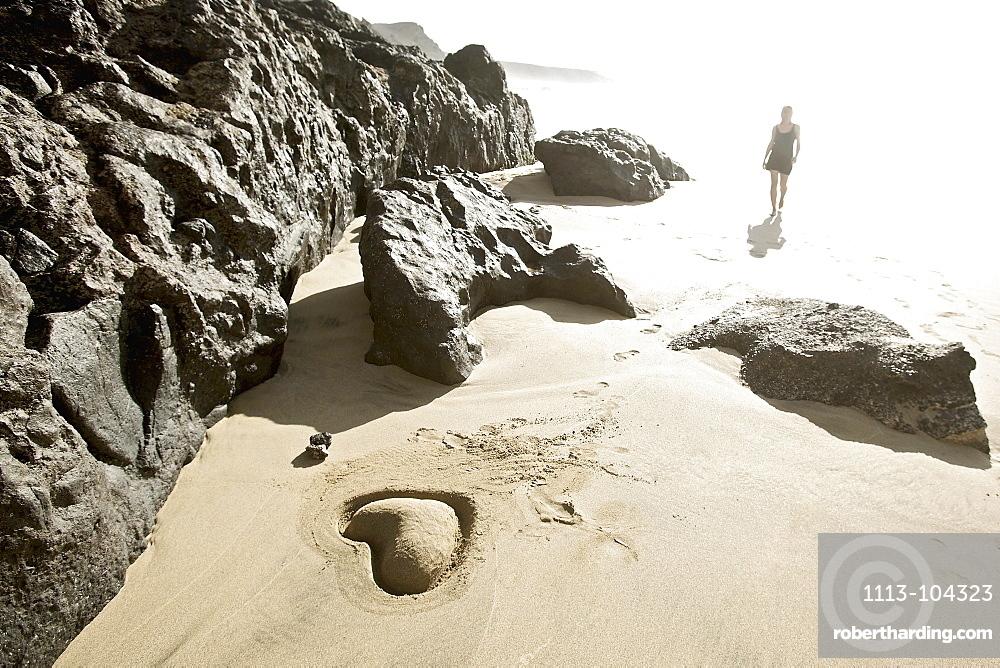 Young woman at beach near heart shaped, Fuerteventura, Spain