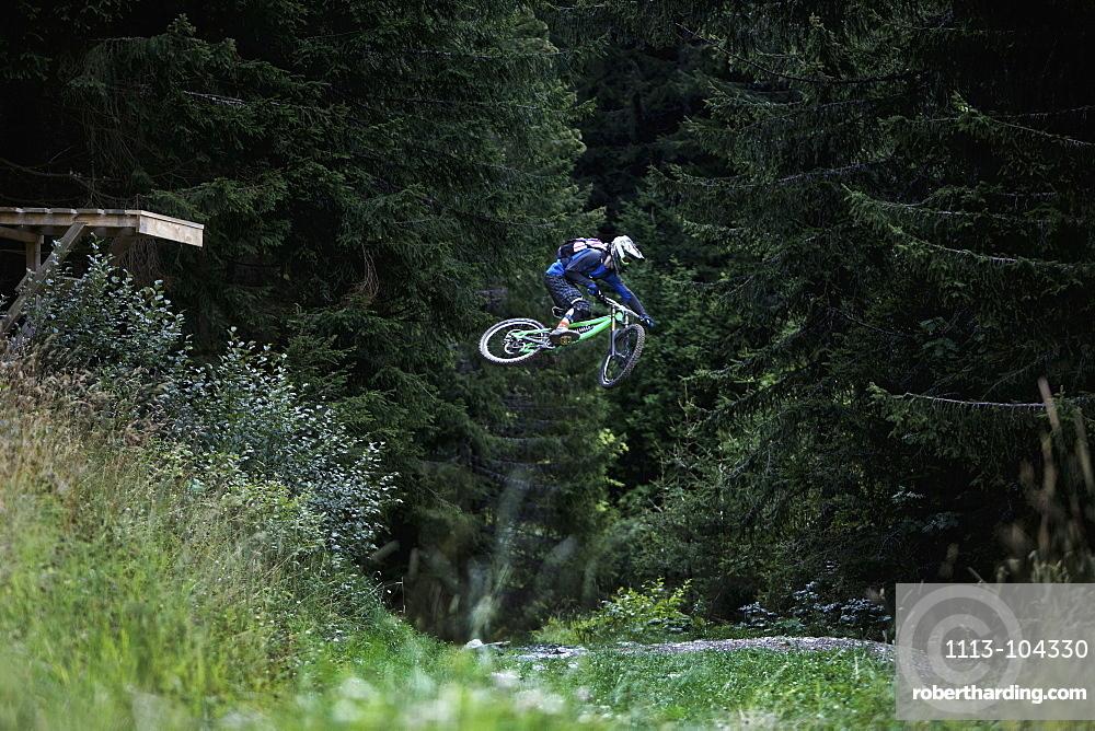Freeride mountain biker jumping, Chatel, Haute-Savoie, France