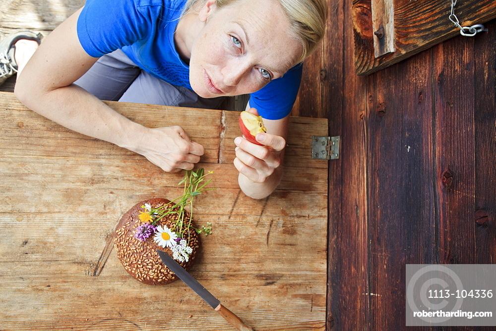 Woman enjoying a snack on a farm, Kloaschau Valley, Bayrischzell, Bavaria, Germany