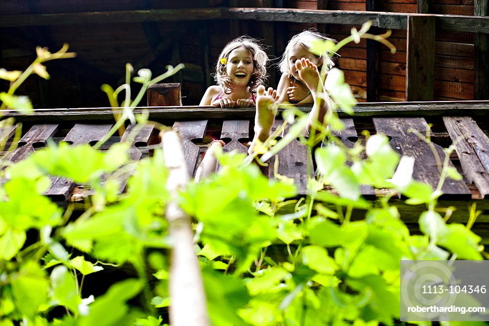 Two girls standing on a balcony, Styria, Austria