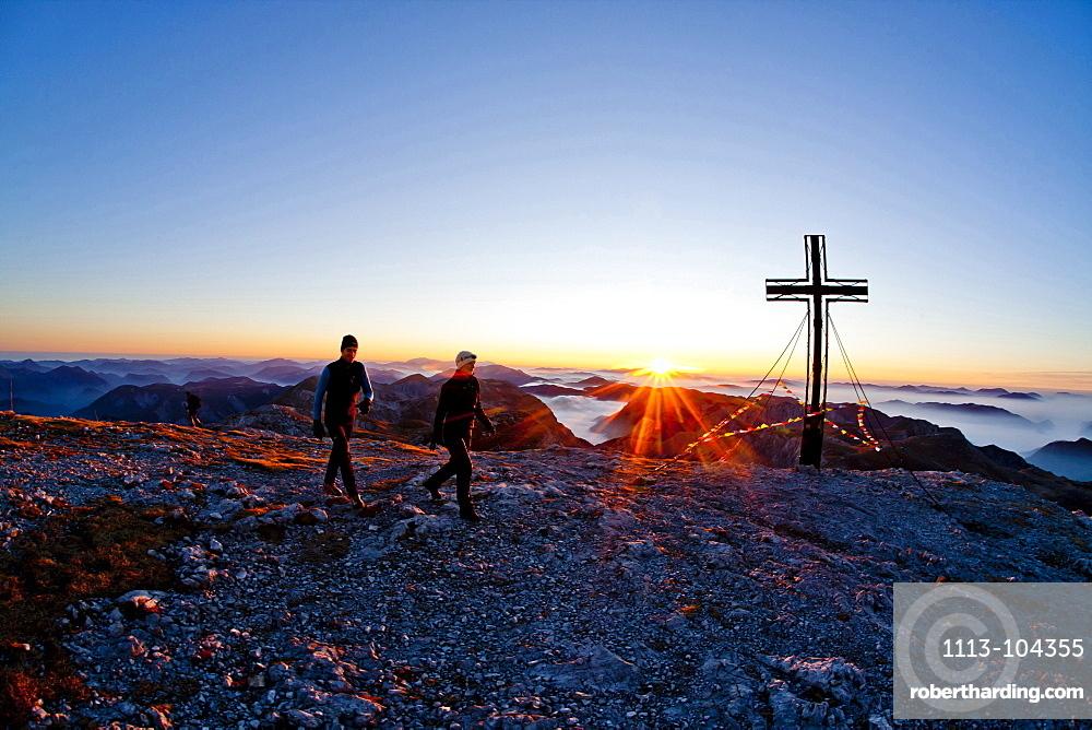 Two hikers at summit of Hochschwab mountain at sunrise, Hochschwab, Styria, Austria