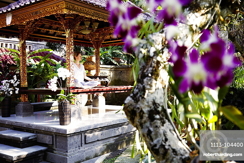Woman meditating in a pavilion, Ubud, Bali, Indonesia
