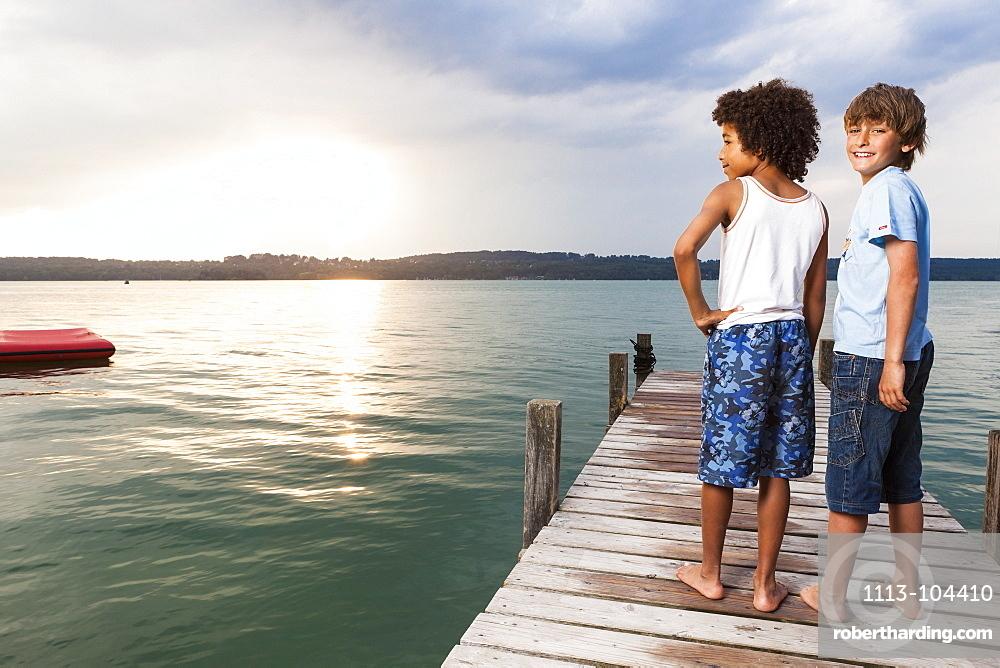 Two boys on a jetty at lake Starnberg, Upper Bavaria, Germany