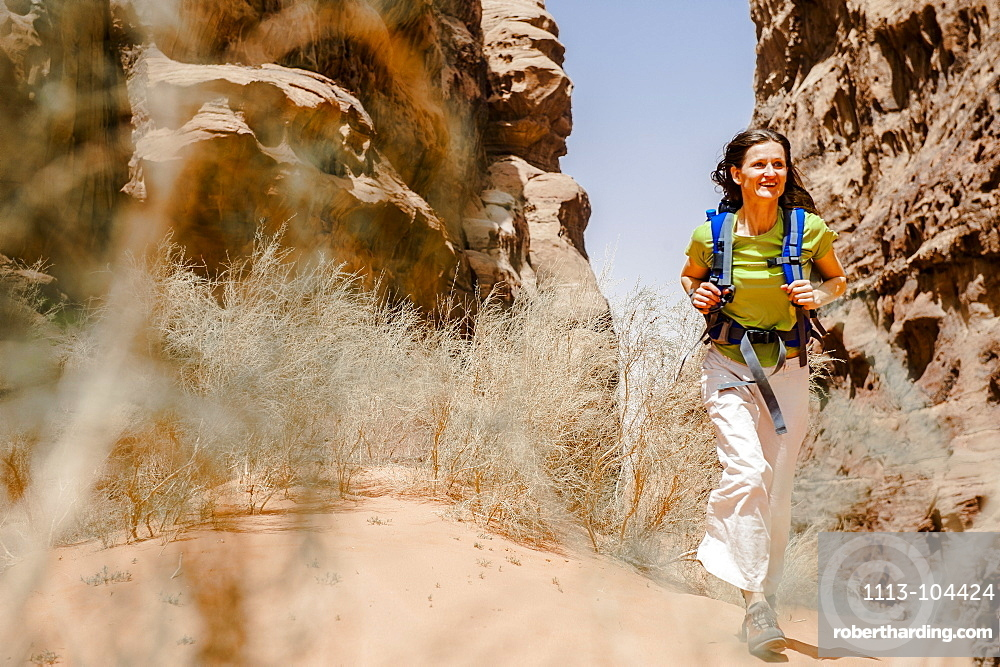 Woman hiking through a gorge, Wadi Rum, Jordan, Middle East