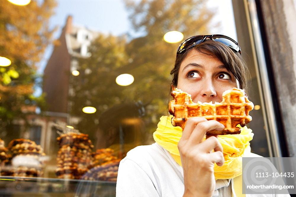 Woman eating a Belgian waffle, Liege, Wallonia, Belgium
