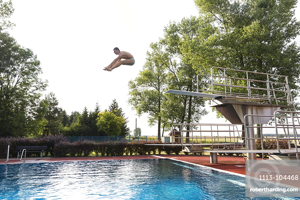 Man jumping from diving board, Leipzig, Saxony, Germany