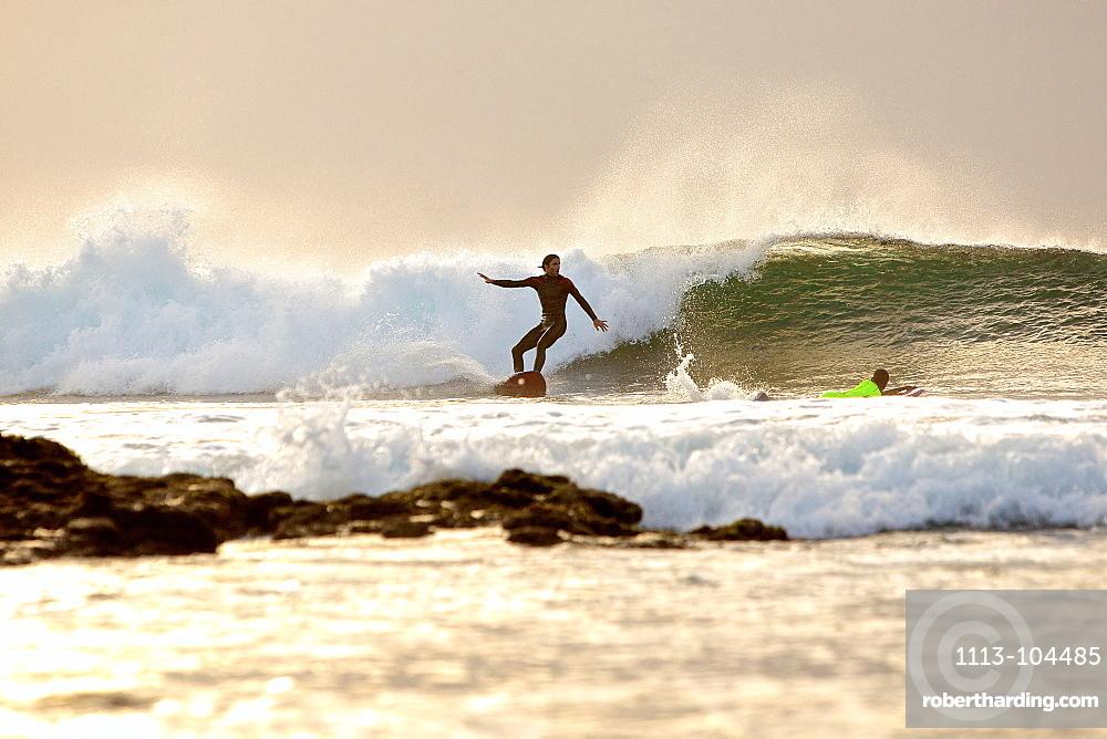 Surfers riding a wave, Praia, Santiago, Cape Verde