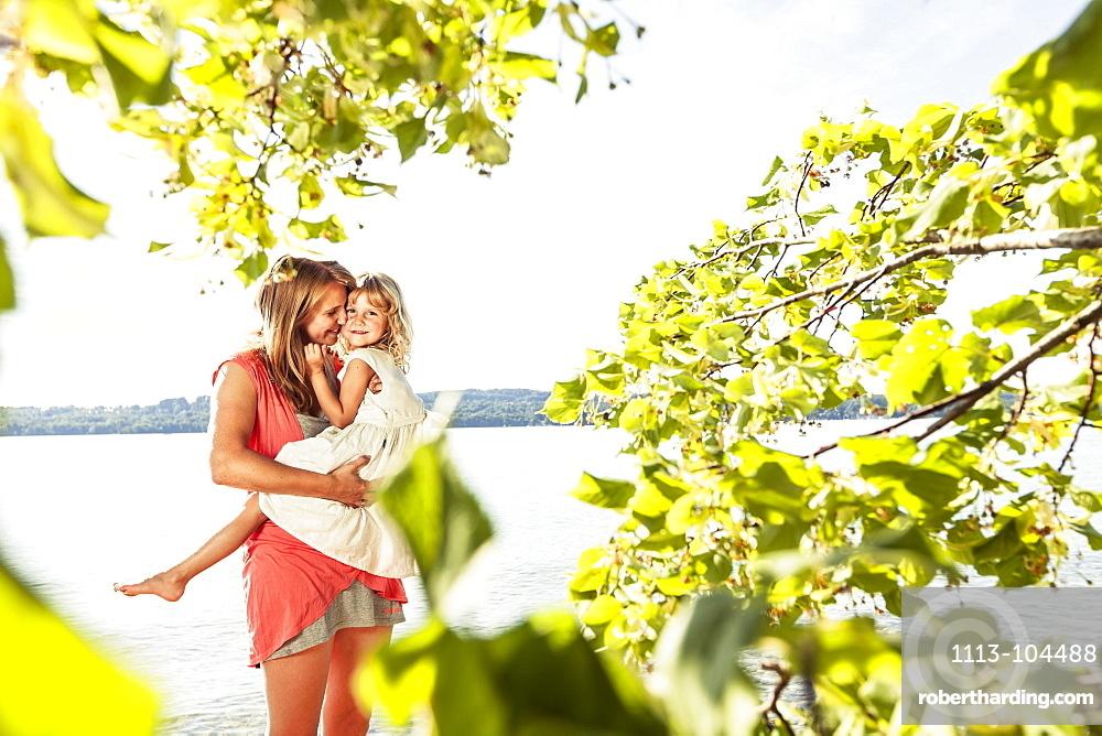 Mother carrying daughter in her arms, lake Starnberg, Berg, Upper Bavaria, Germany