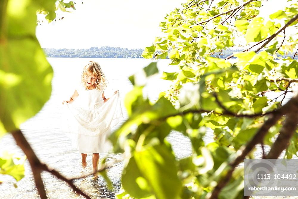 Girl wearing a summerdress standing in lake Starnberg, Berg, Upper Bavaria, Germany