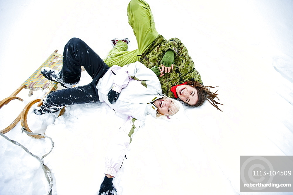 Two laughing young women in snow
