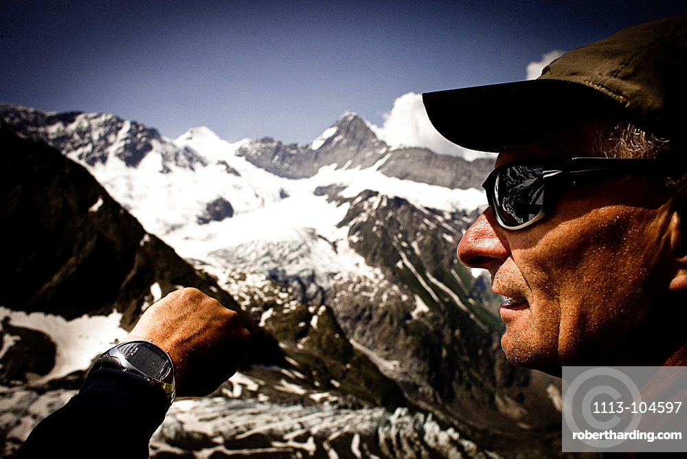 Hiker having a look at a watch, on the way to Schreckhorn hut, Lower Grindelwald glacier, Eiger and Moench in the background, Bernese Oberland, Switzerland
