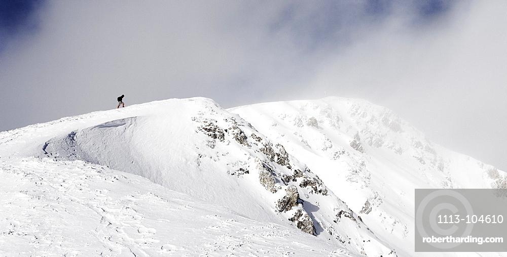 Hiker climbing on a snowy peak, ascend to Unnutz Mountain (2078 m), Rofan Mountains, Tyrol, Austria