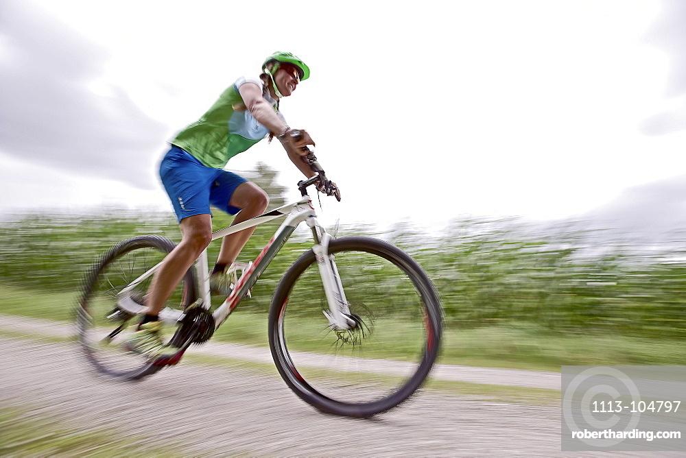 Woman bicycling, Chiemgau, Bavaria, Germany