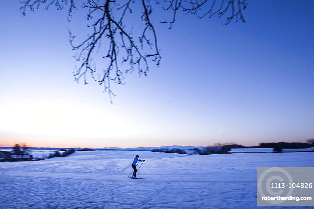 Young woman cross-country skiing at sunset, Allgaeu, Bavaria, Germany