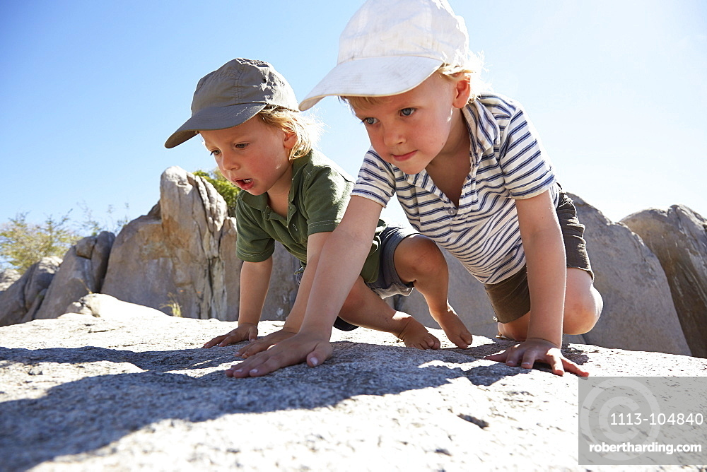 Two boys climbing over rocks, Kubu Island, Makgadikgadi Pans National Park, Botswana
