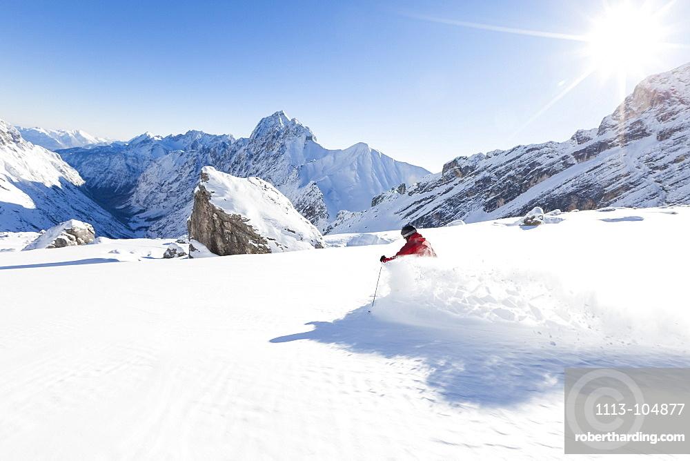 skier in deep powder snow, Zugspitze, overlooking Reintal Valley and Hochwanner, Upper Bavaria, Germany