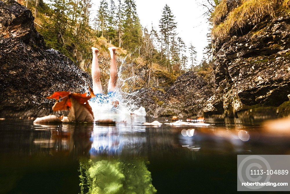 young man jumping from a cliff into mountain stream, Eschenlohe, Upper Bavaria, Germany