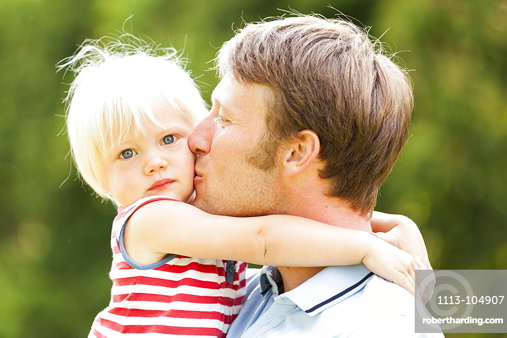 young father kissing his two-year-old daughter, Speyer, Rheinland-Pfalz, Germany