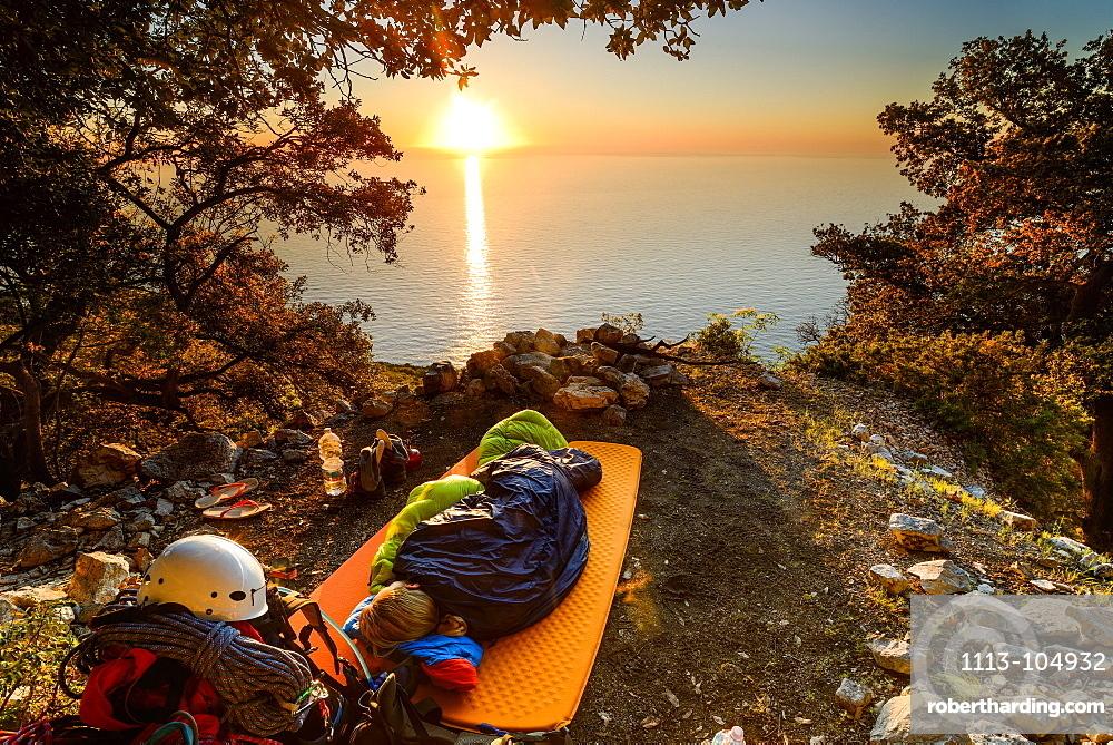 Young woman sleeping in her sleeping bag at sunrise near the bay Cala Biriola, Trekking- and climbing gear visible, Golfo di Orosei, Selvaggio Blu, Sardinia, Italy, Europe
