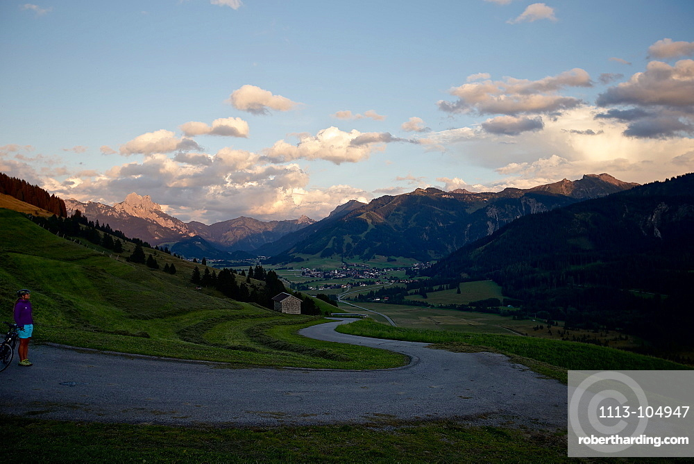 Young female cyclist having a break to enjoy the ambiance, Tannheimer Tal, Tyrol, Austria