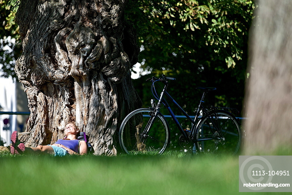 Young female cyclist relaxing against a big tree, Kempten, Bavaria, Germany