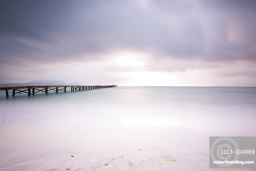 Long exposure of a wooden pier on Playa de Muro beach in the morning mood. The sky is overcast and fog lies over the Bay of Alcudia. Alcudia, Mallorca, Balearic Islands, Spain