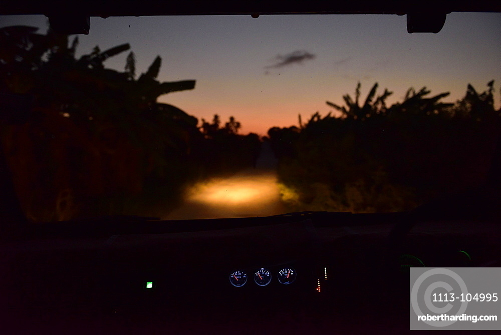 View through the windshield of a car during a bush drive at night in Kigamboni, Tanzania, Africa