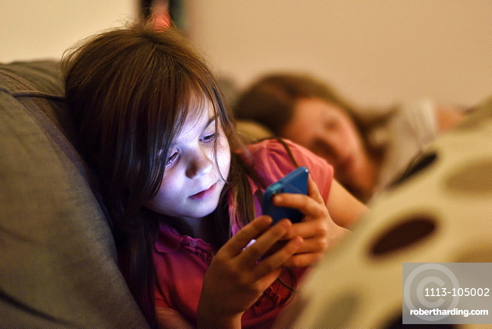Young girl with smartphone on the sofa, Hamburg, Germany, Europe