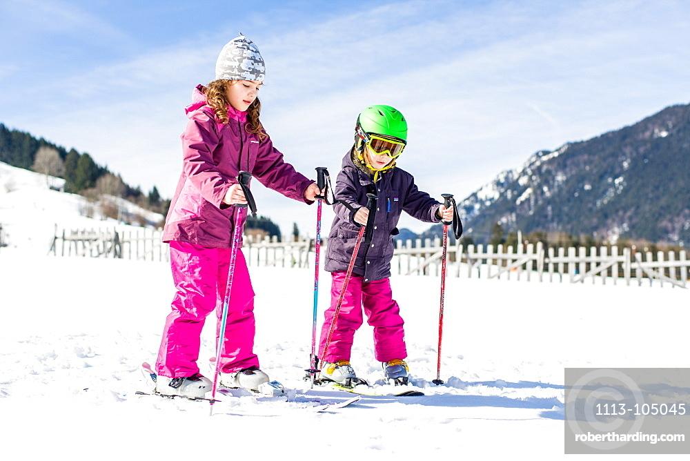 boy and girl skiing on the slope, Pfronten, Allgaeu, Bavaria, Germany