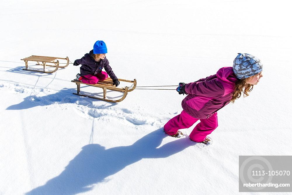 Girl pulling boy on his sled, Pfronten, Allgaeu, Bavaria, Germany