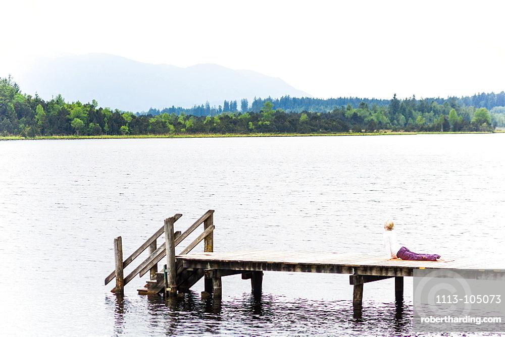 woman is making yoga on the boardwalk, sun salute, Kirchsee, Bad Toelz, Bavaria, Germany
