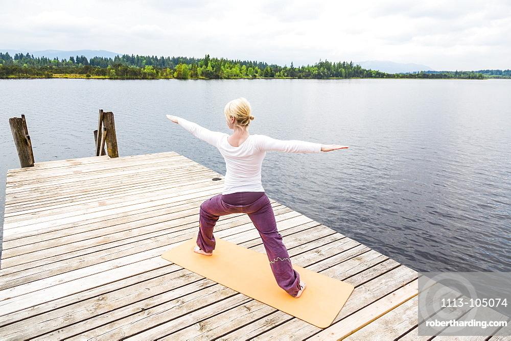 woman doing Yoga on the jetty, sun salute, Kirchsee, Bad Toelz, Bavaria, Germany
