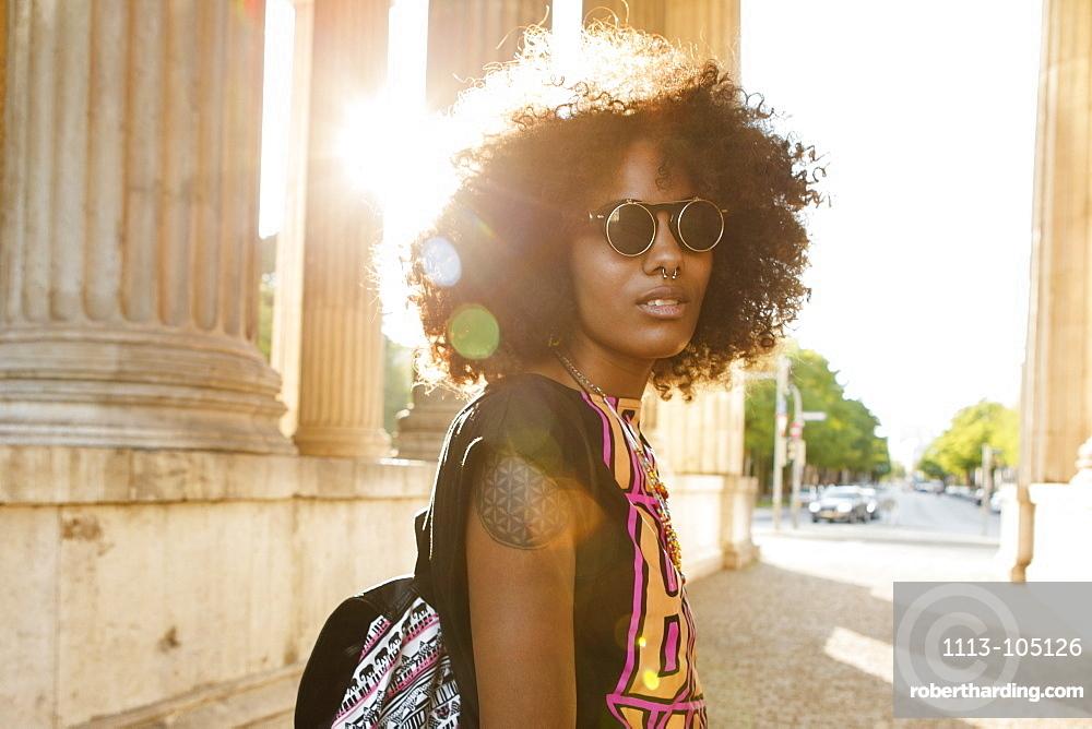 Young afro-american woman in backlight scenery at Koenigsplatz, Munich, Bavaria, Germany