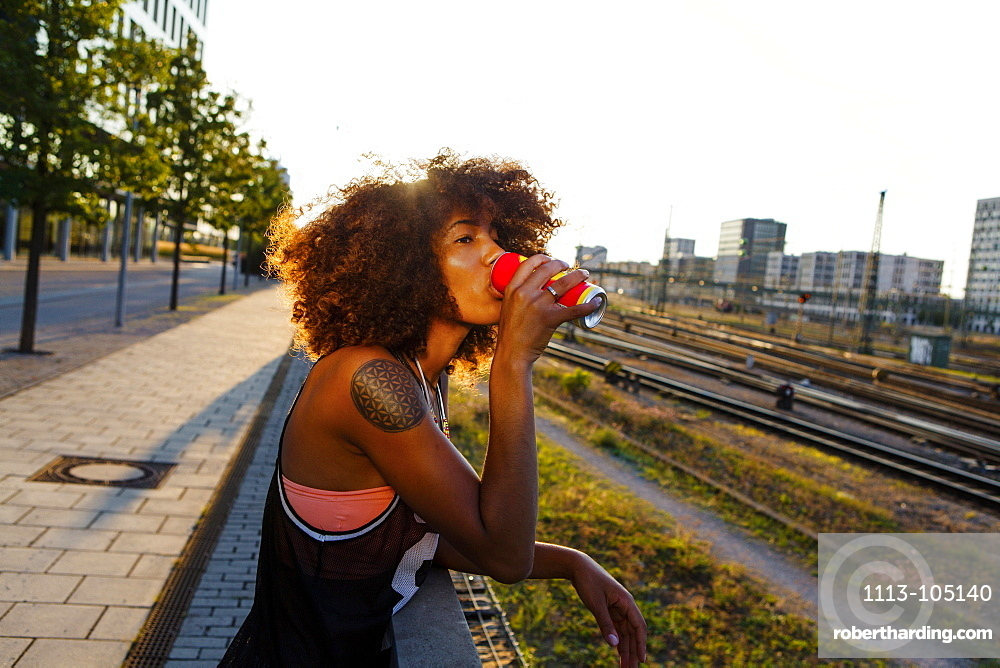 Young afro-american woman drinking from a can in urban scenery with train tracks, Hackerbruecke Munich, Bavaria, Germany