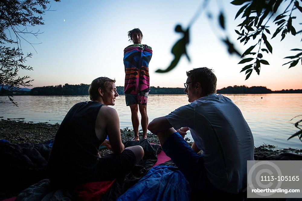 Three young men at a lake, Freilassing, Bavaria, Germany