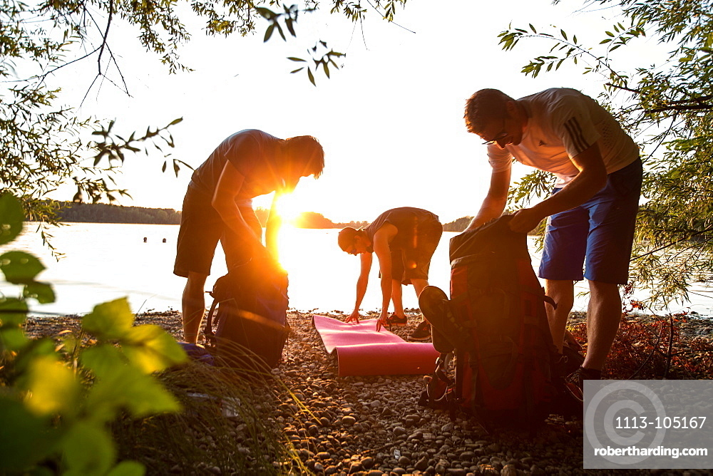 Three young male campers preparing their stuff at a lake, Freilassing, Bavaria, Germany