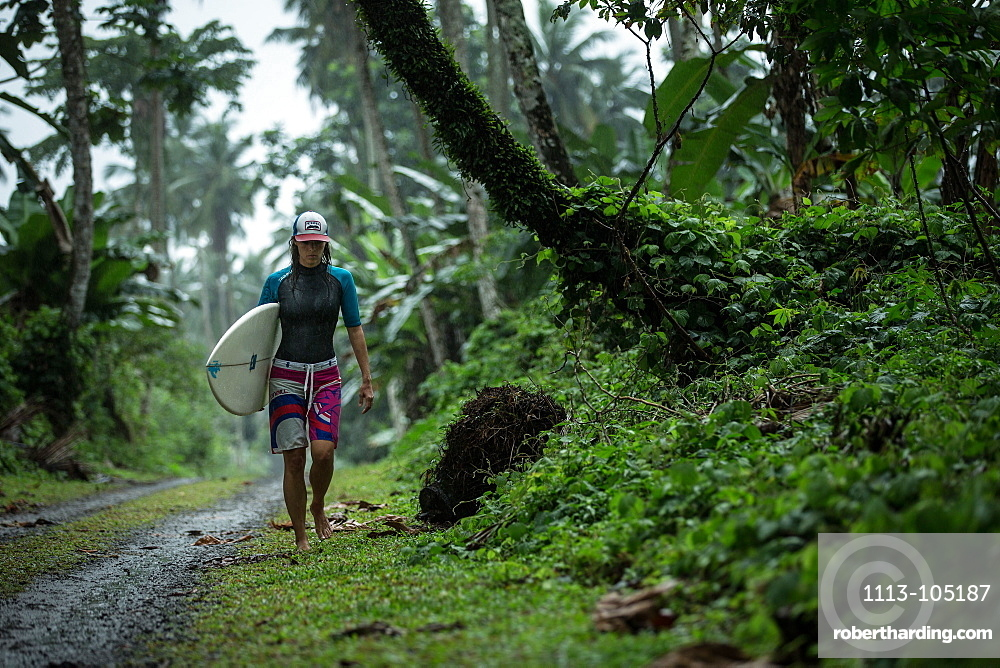Young female surfer walking on a simple street through a forest, Sao Tome, Sao Tome and Principe, Africa