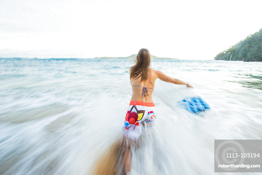 Young female surfer running into the sea, Sao Tome, Sao Tome and Príncipe, Africa