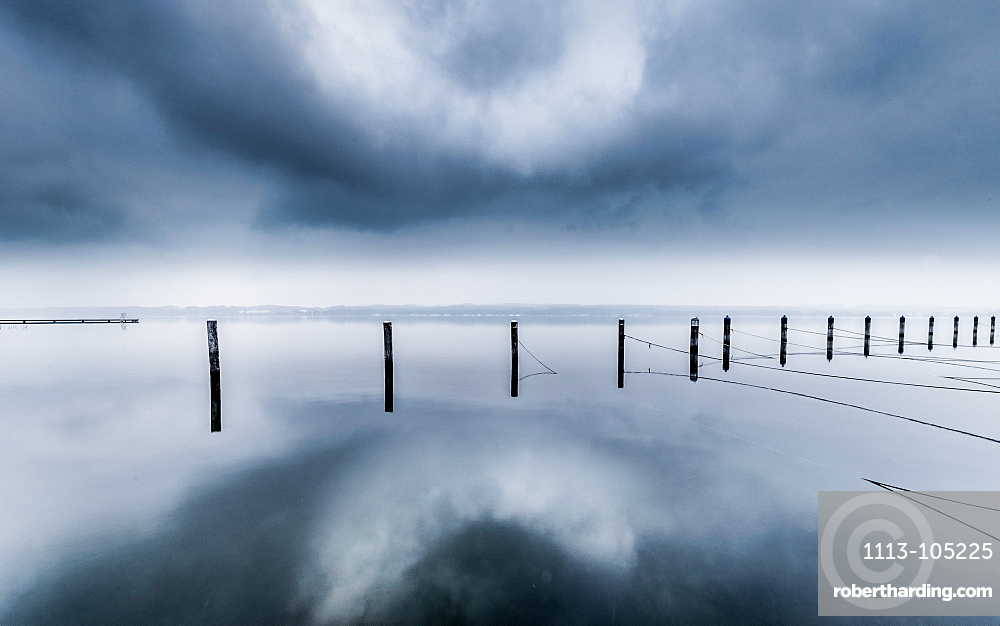 Reflecting UFO cloud over abandoned marina on a foggy winter morning at Lake Starnberg, Bavaria, Germany