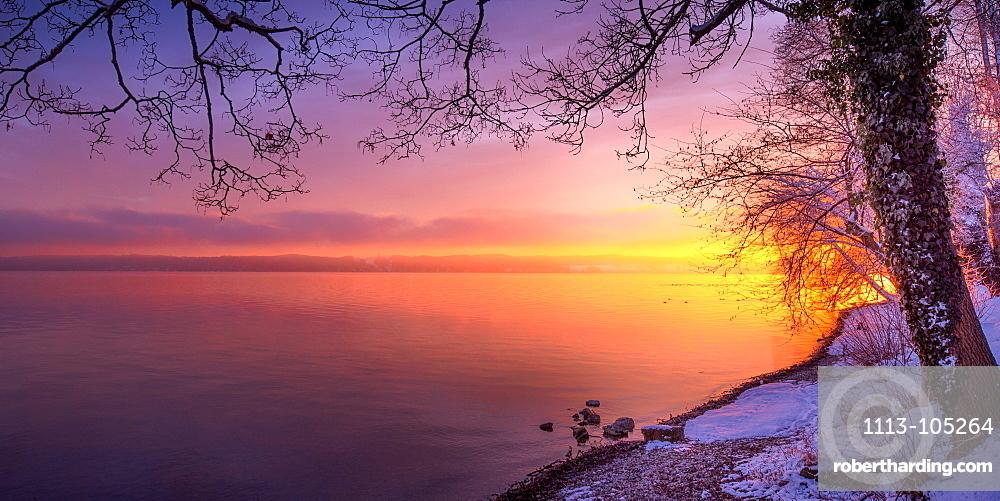 Winter morning with snow at sunrise on Lake Starnberg, Bernried, Bavaria, Germany
