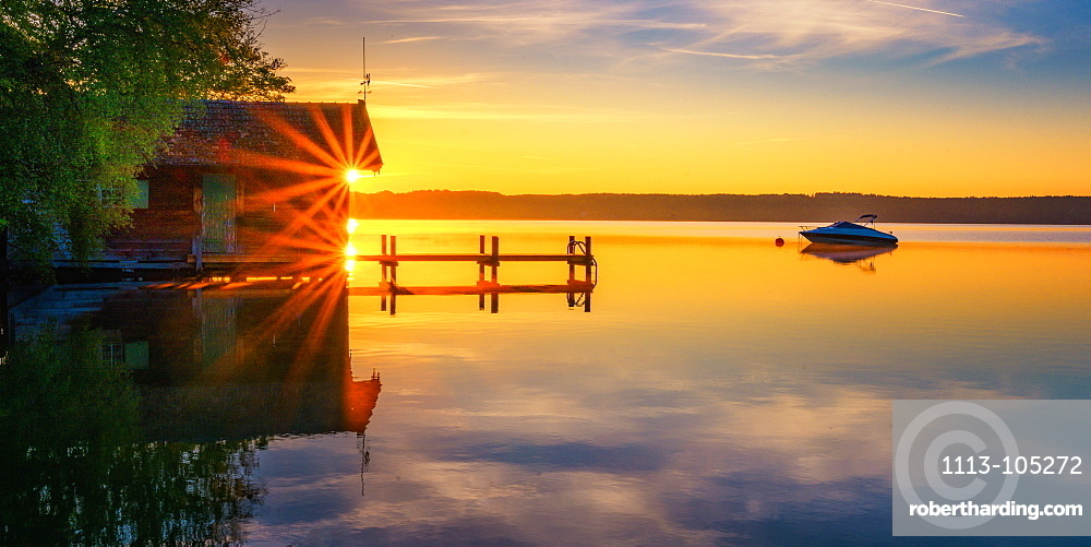 Boothaus silhouette with jetty at sunrise on Lake Starnberg, Bavaria, Germany