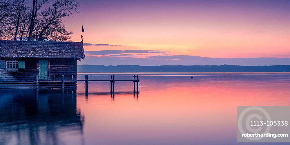 Boat hut and jetty at sunrise on Lake Starnberg, Bavaria, Germany
