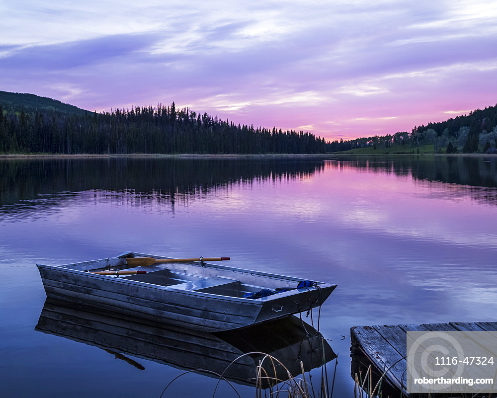 A wooden rowboat sits beside a dock on a tranquil lake reflecting the pink of a sunset, Lac Le Jeune Provincial Park, Kamloops, British Columbia, Canada