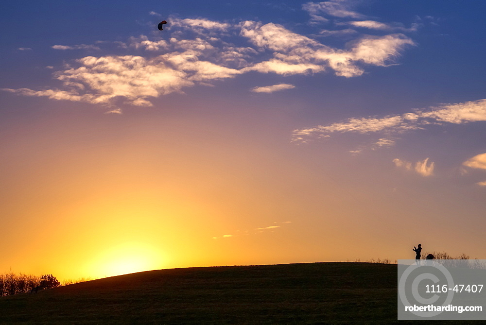 Glowing sun sinking behind a hill while a silhouetted person stands flying a kite, South Shields, Tyne and Wear, England
