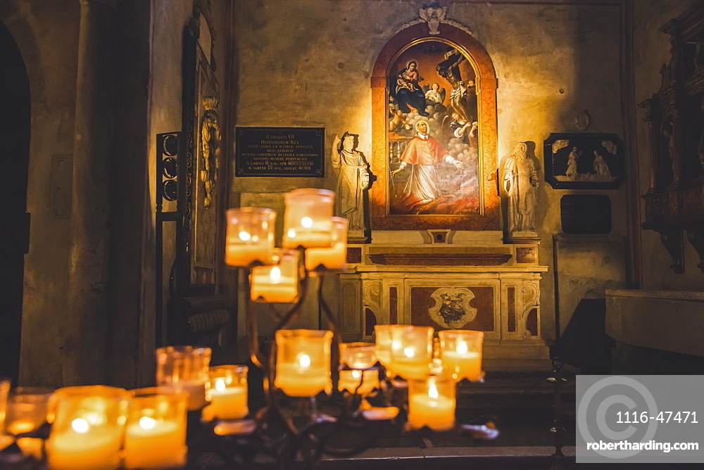 Lit candles and artwork in a cathedral, Italy
