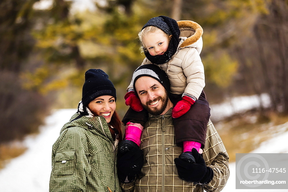 A young family hiking outdoors with their young daughter during a winter family outing: Fairmont, British Columbia, Canada