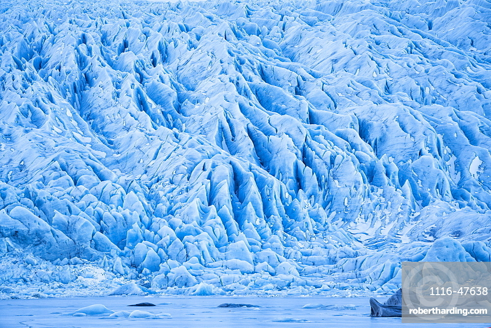 Glacier along the Southern shore of Iceland., icebergs are frozen into the lagoon at the base of it, Iceland