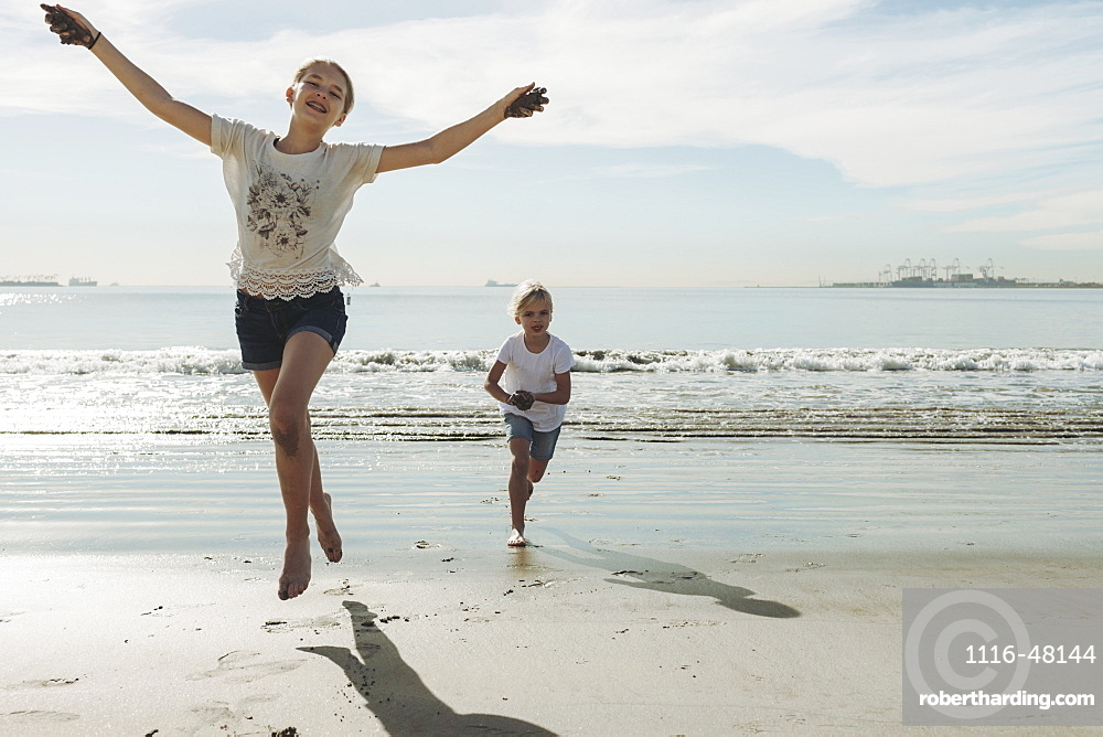 Two sisters running and playing on a beach, the oldest one in front making eye contact with the camera and she leaps into the air, Long Beach, California, United States of America